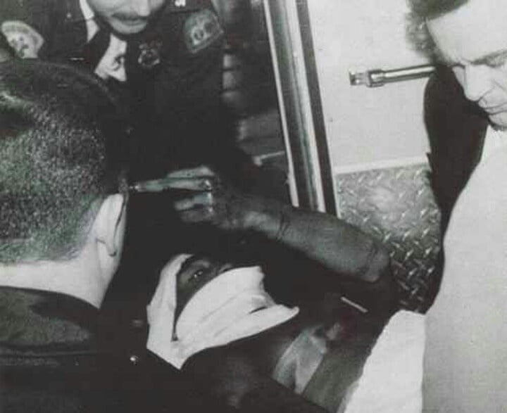 Tupac holding his middle finger high after being shot.
