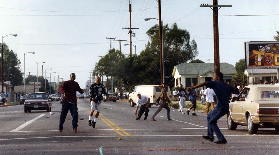 4-29-1992 Young boy in crosswalk has just thrown a rock at photographer's car as others run around the intersection of Florence and Normandie outside Tom's Liquor and Deli. The store was later looted. / latimes.com